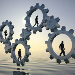 Executives walking inside gears at sea at dawn demonstrate the power of cooperation and synergy.